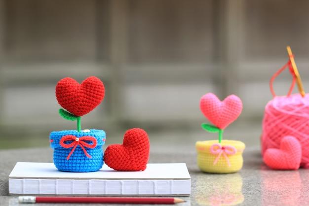 Coração artesanal de crochê com um gancho e um novelo de lã