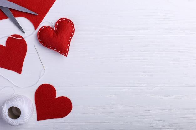 Coração artesanal de feltro vermelho ao lado de linhas e uma agulha sobre uma mesa branca. conceito de dia da mulher, cópia espaço.