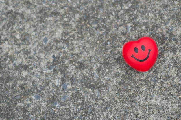 Coração atraente vermelho fundo de rosto sorridente de cimento