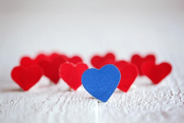 Coração azul e muitos corações vermelhos em fundo branco. valentin