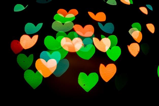 Coração bokeh de fundo, amor e conceito de dia dos namorados. corações brilhantes multicoloridos luz