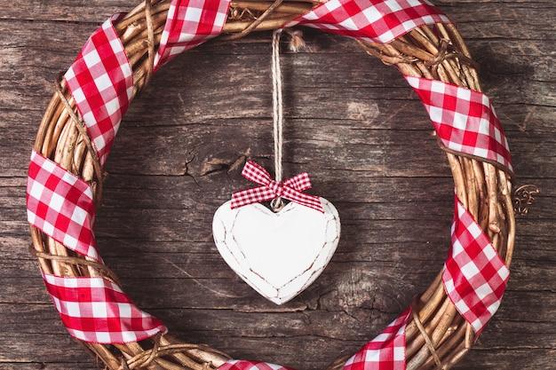 Coração branco e coroa de flores sobre fundo de madeira velho