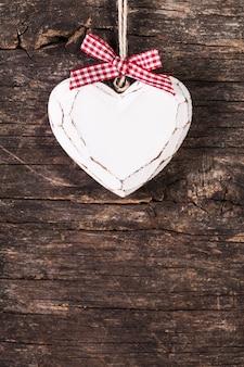 Coração branco esculpido sobre fundo de madeira antigo, decoração de dia dos namorados