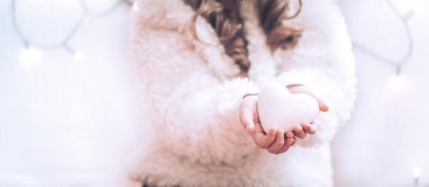 Coração branco nas mãos de uma menina