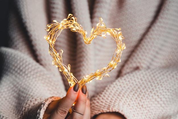 Coração brilhante nas mãos de uma mulher. feliz dia dos namorados. xadrez, conforto, inverno, coração de guirlanda nas mãos de uma mulher. feliz dia dos namorados