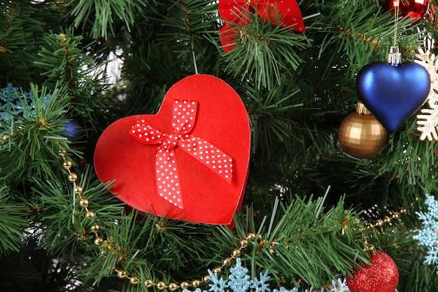 Coração - caixa de presente no fundo da árvore de natal, close-up