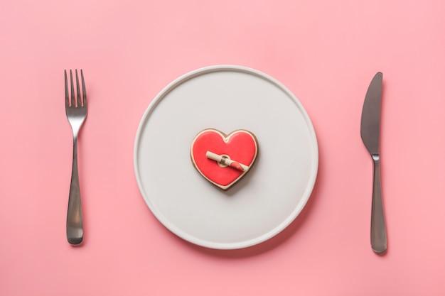 Coração caseiro em forma de biscoitos para dia dos namorados em chapa branca. cenário de mesa em rosa. conceito. vista de cima. postura plana.