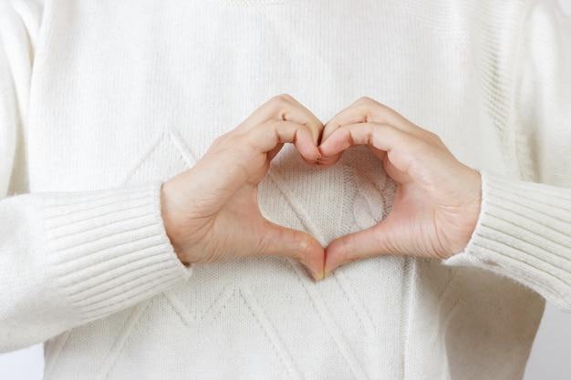 Coração com as mãos. a menina está de mãos dadas em forma de coração