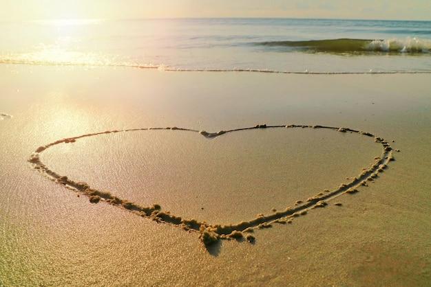 Coração com as ondas batem na praia e a luz do sol na manhã de verão