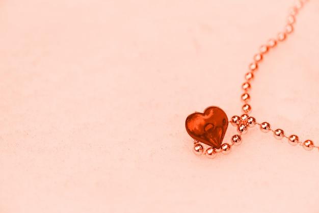 Coração com corrente de ouro na neve no dia dos namorados