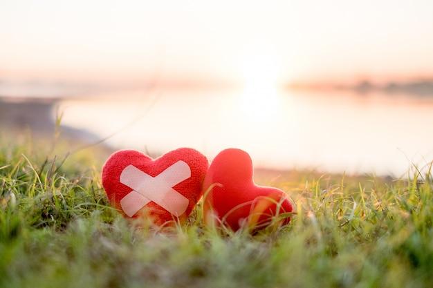 Coração com gesso e coração vermelho no fundo
