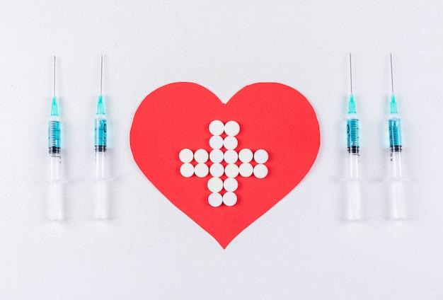Coração com medicamento dentro com seringas
