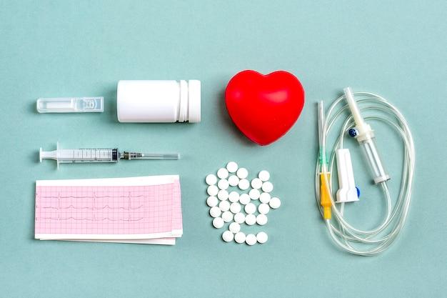Coração, comprimidos médicos, sistema conta-gotas, eletrocardiograma, seringa, cápsulas em cinza