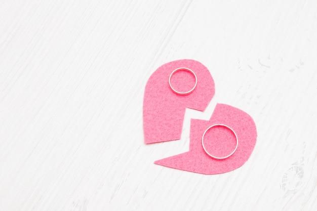 Coração cortado feito de feltro e alianças de casamento, divórcio, coração partido, divórcio, fundo claro, espaço de cópia