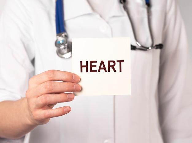 Coração da palavra no papel nas mãos do médico, conceito médico.