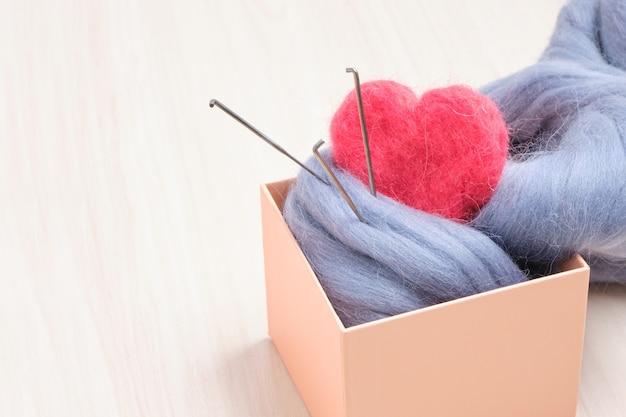 Coração de agulha de lã feltrada rosa e um novelo de lã em uma caixa de presente sobre a mesa
