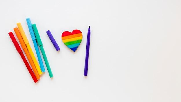 Coração de arco-íris com canetas de feltro na mesa branca