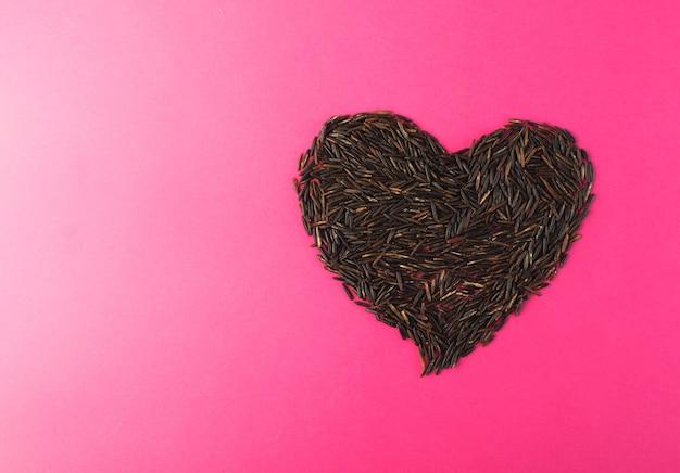 Coração de arroz selvagem preto cru na vista superior do fundo de papel rosa. cereais de arroz do canadá com dieta saudável