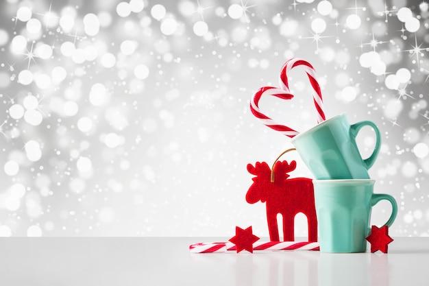 Coração de bastão de doces de natal no copo, estrelas vermelhas e forma de veado no traçado de recorte abstrato incluído. cartão de felicitações, espaço de cópia