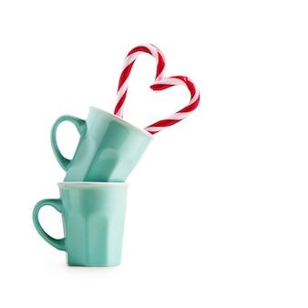 Coração de bastões de doces de natal no copo isolado no traçado de recorte de fundo branco incluído. elemento de design