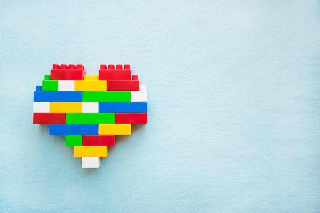 Coração de blocos de plástico coloridos sobre um fundo azul