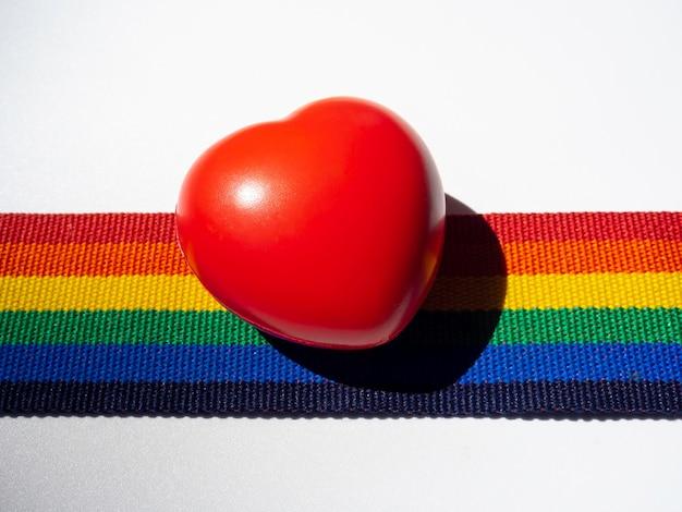 Coração de bola vermelha de clpose-up na fita de listra do arco-íris, isolada no fundo branco. conceito lgbt com cores do orgulho e faixa da bandeira do arco-íris. fundo de banner lgbt.