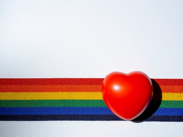 Coração de bola vermelha na fita de listra do arco-íris, isolada no fundo branco com espaço de cópia. conceito lgbt com cores do orgulho e faixa da bandeira do arco-íris. fundo de banner lgbt.