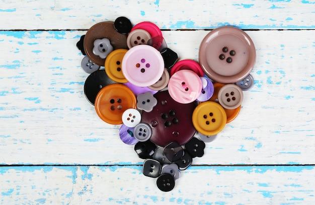 Coração de botões de costura em fundo de madeira