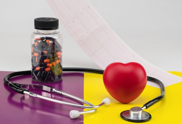 Coração de brinquedo com pílulas e estetoscópio em um fundo colorido cuidados de cardiologia do coração