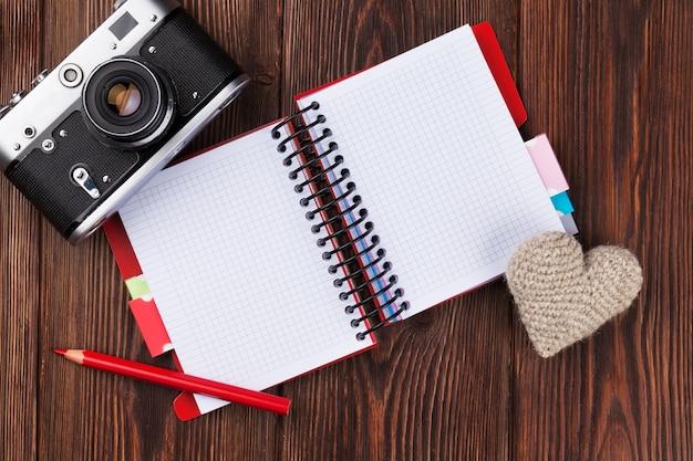 Coração de brinquedo de dia dos namorados, câmera retro e bloco de notas para o seu texto. vista superior em mesa de madeira