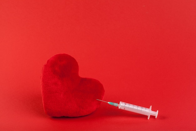 Coração de brinquedo de tecido vermelho e seringa, conceito de saúde