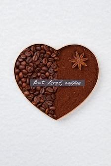 Coração de café isolado na superfície branca símbolo decorativo do amor feito com metade dos grãos de café e do pó de café instantâneo com erva-doce.