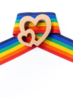 Coração de casal de madeira na fita de listra do arco-íris, isolada no fundo branco, com espaço de cópia, estilo vertical. conceito lgbt com cores do orgulho e faixa da bandeira do arco-íris. fundo de banner lgbt.
