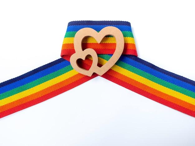 Coração de casal de madeira na fita de listra do arco-íris, isolada no fundo branco. conceito lgbt com cores do orgulho e faixa da bandeira do arco-íris. fundo de banner lgbt.