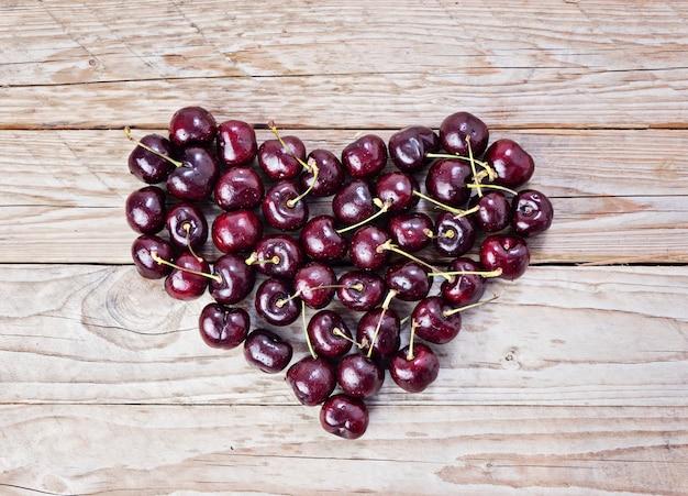 Coração de cereja fresca e madura em um fundo de madeira