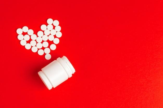 Coração de comprimidos fora do frasco de comprimidos em fundo vermelho, vista superior