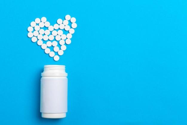 Coração de comprimidos fora do frasco de comprimidos sobre fundo azul, vista superior