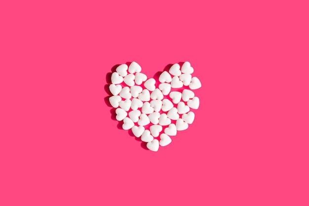 Coração de comprimidos isolados em forma de coração branco. vitaminas para doenças cardíacas cuidados de saúde
