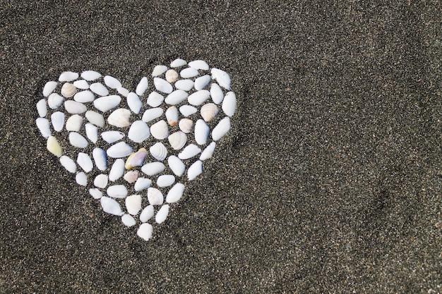 Coração de concha em uma praia à beira-mar na areia preta. plano de fundo romântico. copie o espaço.