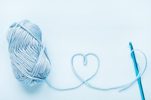Coração de crochê, gancho e novelo de lã em um fundo azul