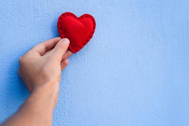 Coração de dia dos namorados vermelho na mão de um cara em um fundo azul