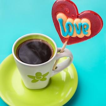 Coração de doces no palito e uma xícara de café.