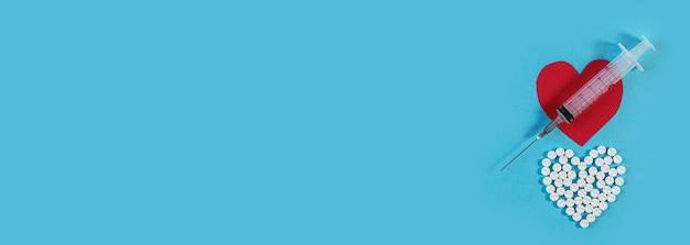 Coração de feltro, formato de coração feito de pílulas e seringa na superfície azul