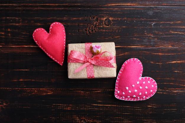 Coração de feltro rosa e presente artesanal em uma mesa de madeira, conceito, banner, espaço de cópia.