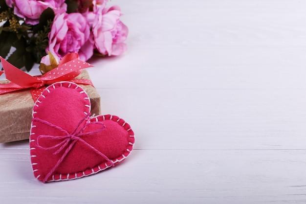 Coração de feltro rosa, flores e presente artesanal em uma mesa de madeira branca