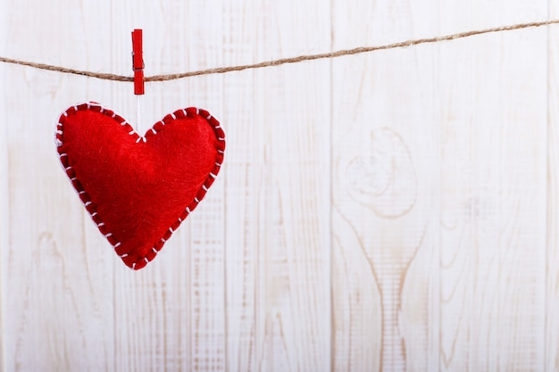 Coração de feltro vermelho em uma corda, sobre fundo branco de madeira