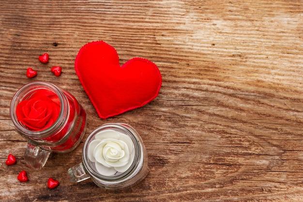 Coração de feltro vermelho, jarra de vidro, rosas e fitas