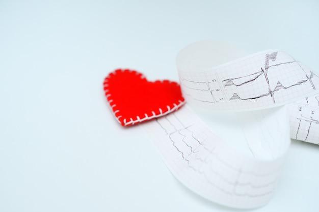 Coração de feltro vermelho na superfície de uma impressão em papel de um gráfico de ecg ou de um eletrocardiograma em uma superfície branca.
