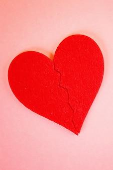 Coração de feltro vermelho quebrado em duas metades no fundo rosa
