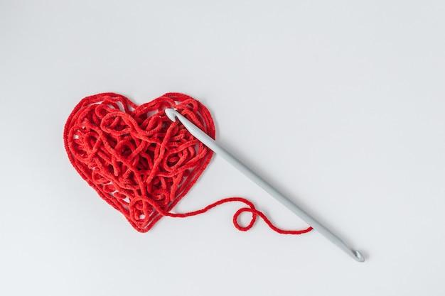 Coração de fio de tricô vermelho em forma de agulha de crochê. conceito mínimo de dia dos namorados.